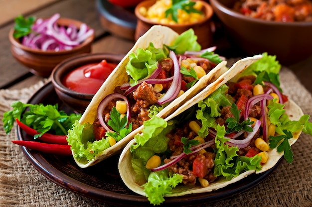 Mexican tacos with meat, vegetables and red onion Free Photo