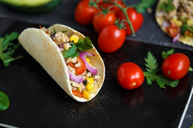 Mexican tacos with pork, vegetables and spices on a black stone plate on a dark background with ingredients for tacos Premium Photo