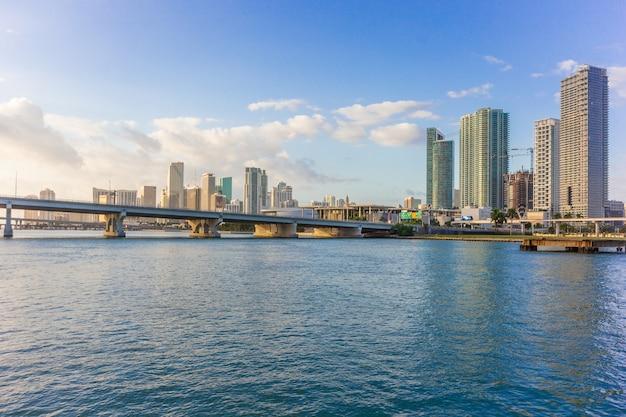 Панорама горизонта города майами на голубом небе облачно и мост через море с отражением Premium Фотографии
