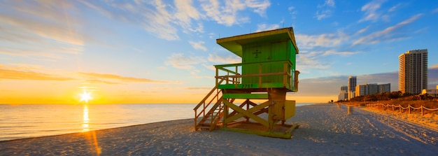 Miami south beach sunrise with lifeguard tower and coastline with colorful cloud and blue sky. Free Photo