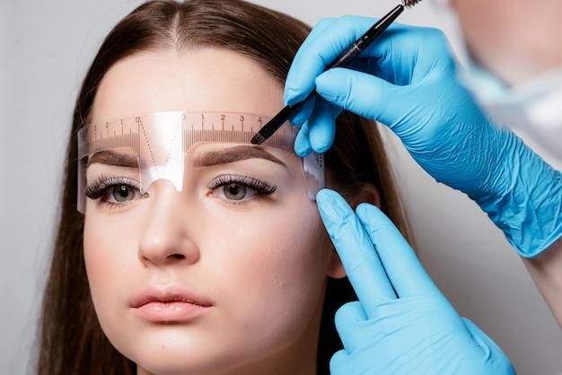 Микроблейдинг бровей работает потоком в салоне красоты. женщина с тонированными бровями. Premium Фотографии