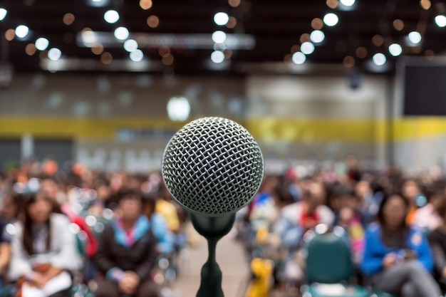 Microphone over the abstract blurred photo of conference hall or seminar room in exhibition center b Premium Photo