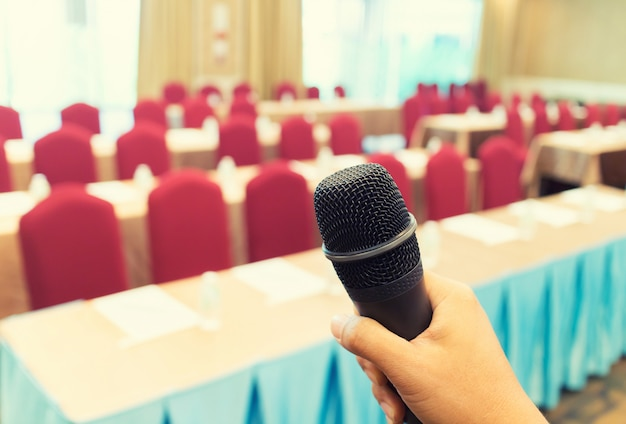 Microphone over the abstract blurred photo of conference hall or seminar room Premium Photo