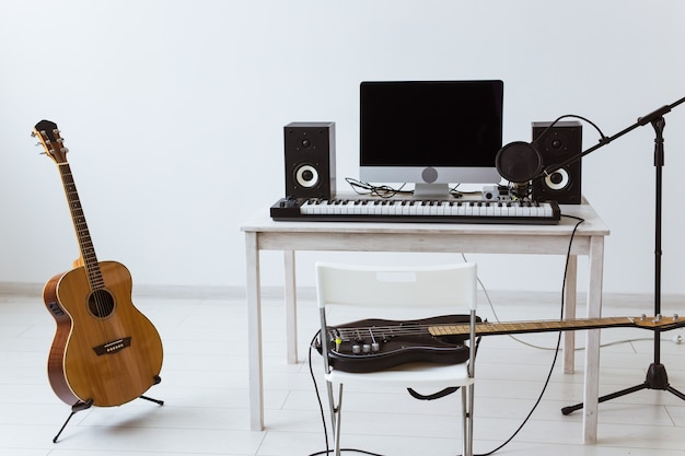 マイク、コンピューター、楽器のギターとピアノの背景。ホームレコーディングスタジオ Premium写真