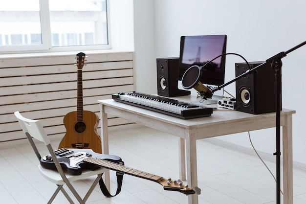 Microphone, computer and musical equipment guitars and piano. home recording studio concept. Premium Photo