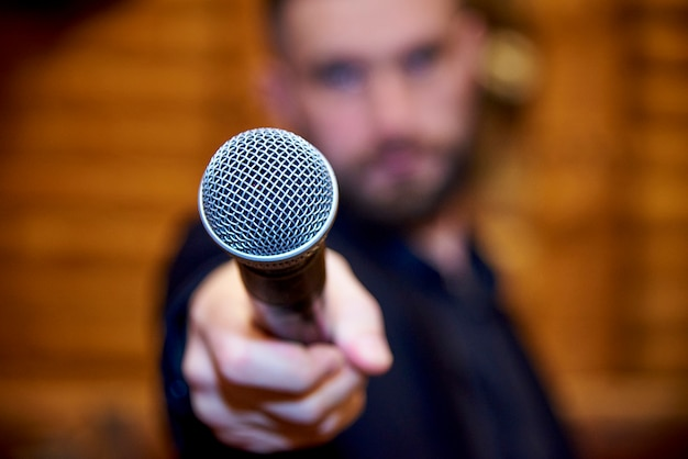 A microphone in the hand of a bearded young man. Premium Photo