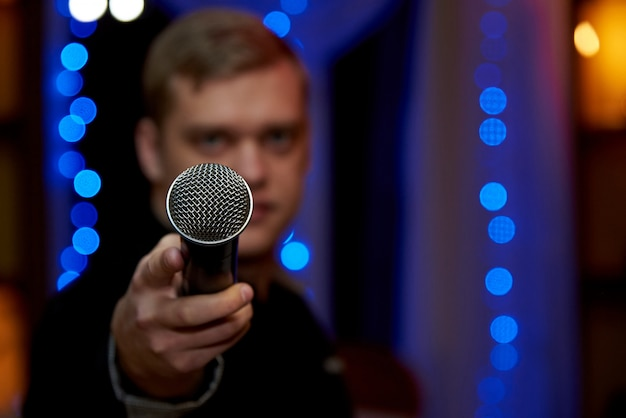 A microphone in the outstretched hand of a blurry young man.copy space. Premium Photo
