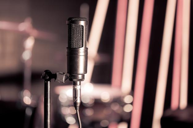 Microphone in recording studio or concert hall close-up, with drum set Premium Photo