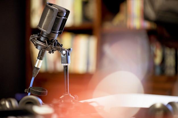 Microfono in uno studio circondato da apparecchiature sotto le luci con uno sfondo sfocato Foto Gratuite