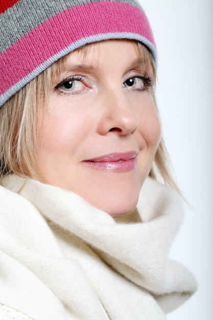 Mid age woman with hot tea wearing winter clothes on a white background Free Photo