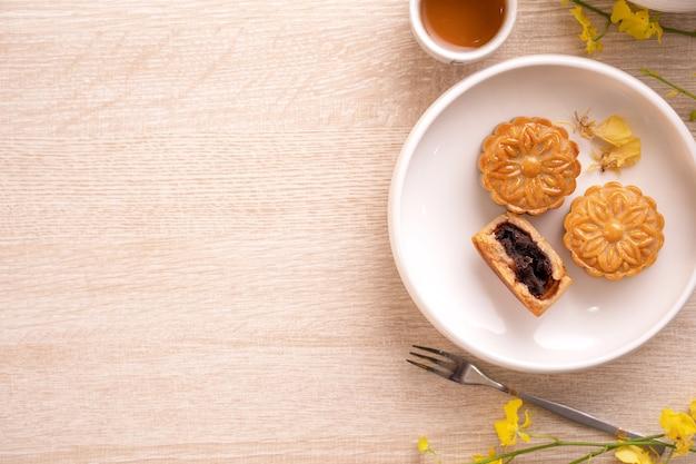 月餅、月餅、コピースペース、上面図、フラットレイ、オーバーヘッドショットと明るい木製のテーブルにお茶セットの中秋節ホリデーコンセプトデザイン Premium写真