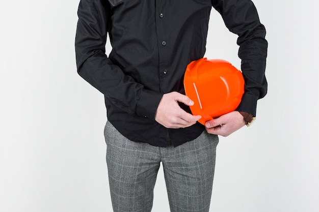 Mid section of an architect holding orange clipboard over white backdrop Free Photo