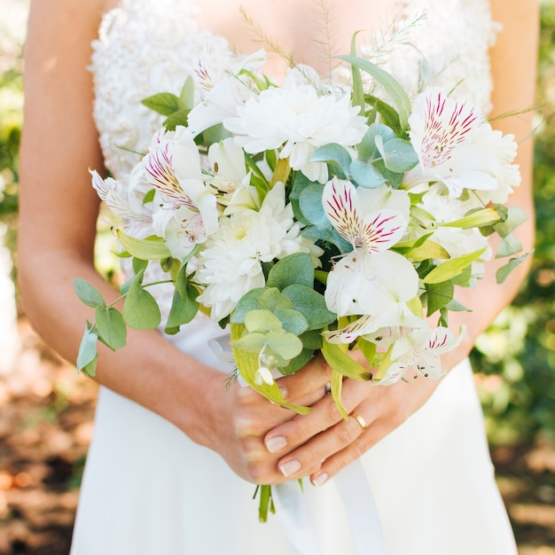 Mid section of a bride's hands holding beautiful flower bouquet Free Photo