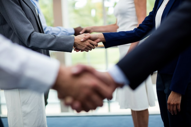 Mid section of business executives shaking hands with each other Premium Photo