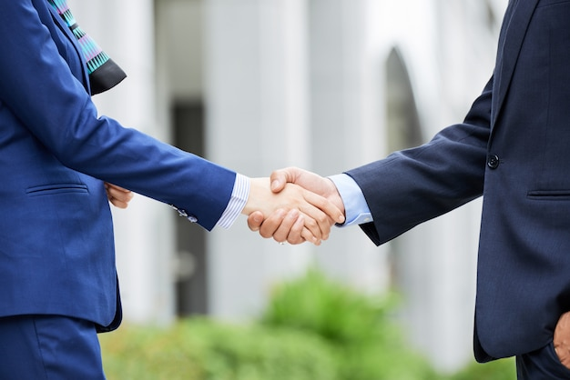 Mid-section of business people shaking hands outdoors Free Photo