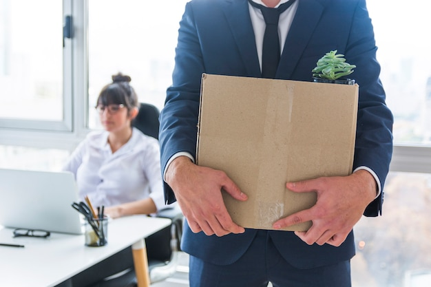 Mid section of businessman carrying cardboard box of stuff for new workplace Free Photo