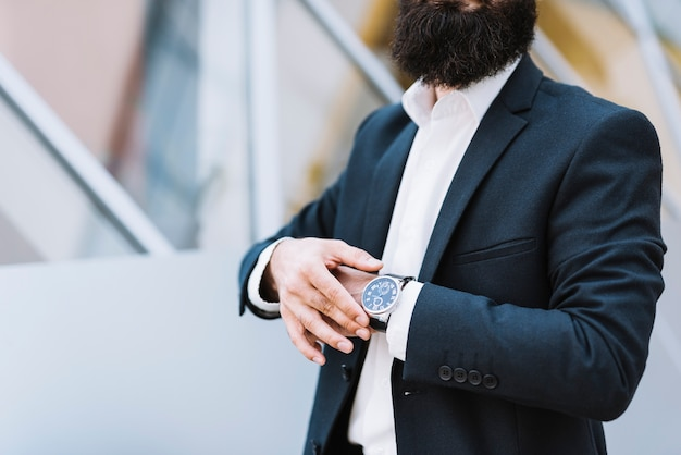Metà di sezione dell'uomo d'affari che tiene orologio da polso sulla sua mano Foto Gratuite