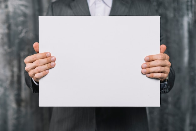 Mid section of a businessman showing blank white placard Free Photo