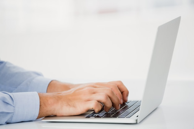 Mid-section of businessman working on laptop Premium Photo