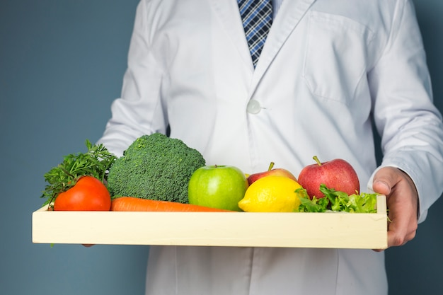 Mid section of a doctor holding wooden tray full of healthy vegetables and fruits against gray background Free Photo