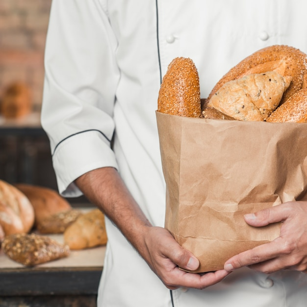 Mid section of maker holding baked breads in paper bag Free Photo
