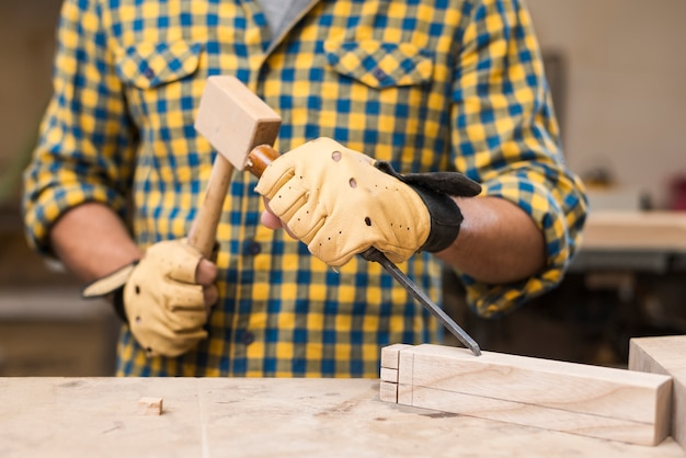 Mid section of male carpenter hitting chisel with hammer on rectangular block Free Photo