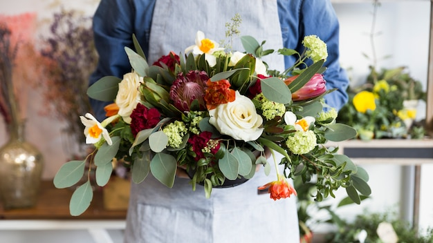 Mid section of a male florist holding beautiful flower vase Free Photo