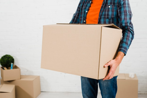 mid section on a man carrying cardboard box in hand photo free download. Black Bedroom Furniture Sets. Home Design Ideas