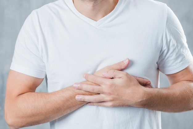 Mid section of a man having chest pain Free Photo