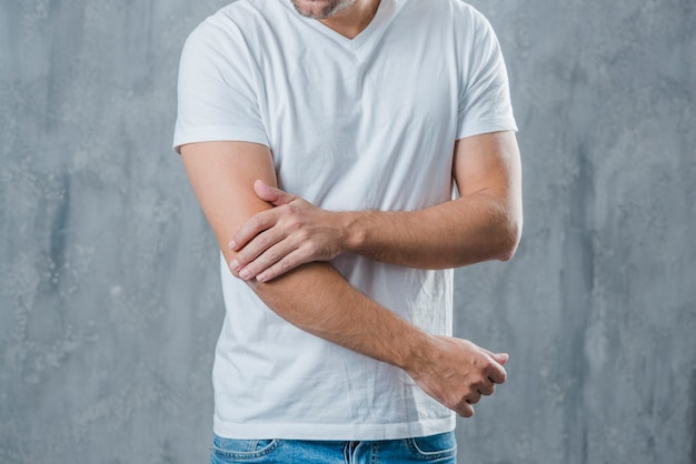 Mid section of a man having elbow pain standing against grey background Premium Photo