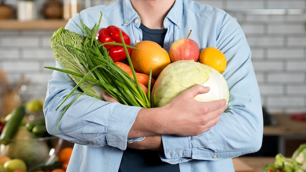 Mid-section of man holding raw vegetables at home Free Photo