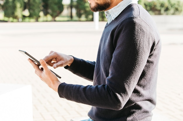 Mid section of a man sitting in the park using touch screen mobile phone Free Photo