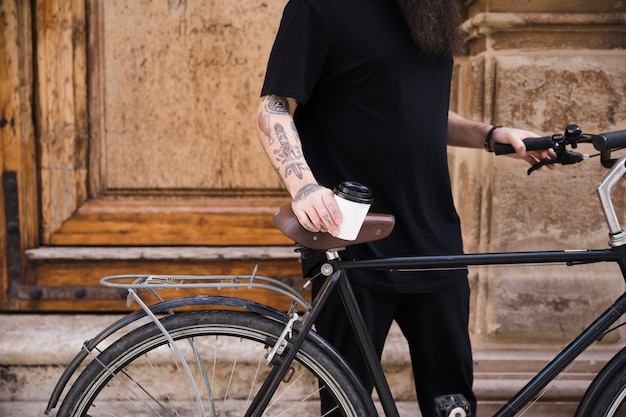 Mid section of a man standing with bicycle holding takeaway coffee cup Free Photo