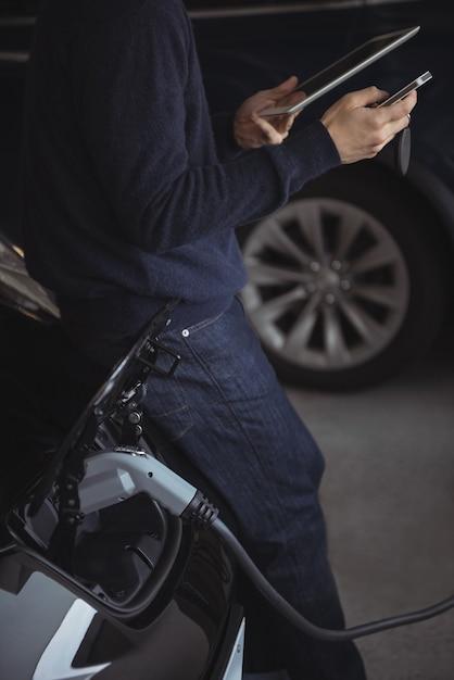 Sezione centrale dell'uomo utilizzando tavoletta digitale e telefono cellulare durante la ricarica di un'auto elettrica Foto Gratuite