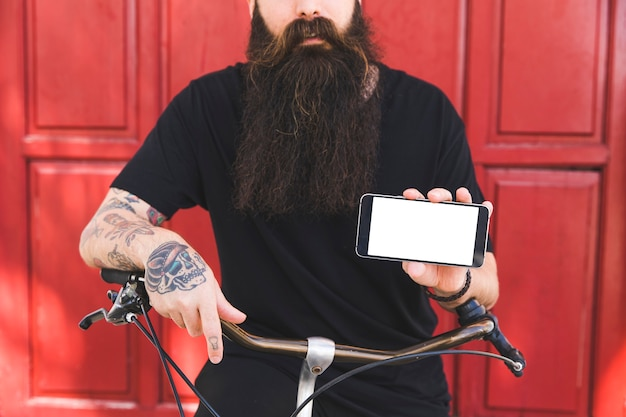 Mid section of a man with tattoo on his hand holding mobile phone in hand Free Photo