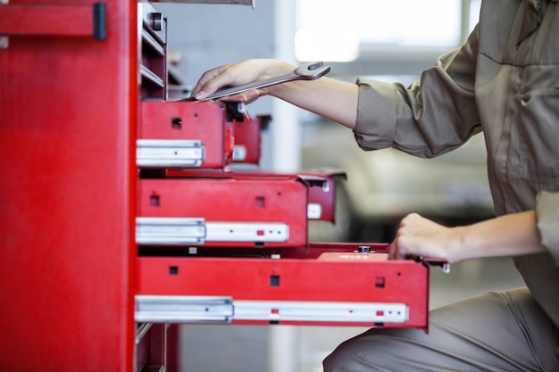 Mid-section of mechanic holding wrench Free Photo