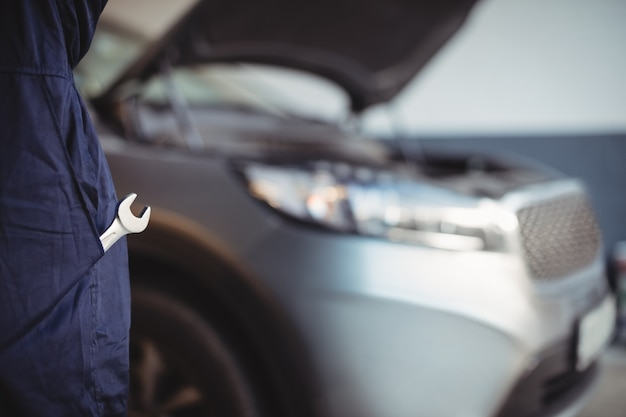 Mid-section of mechanic with a wrench tool in pocket Free Photo