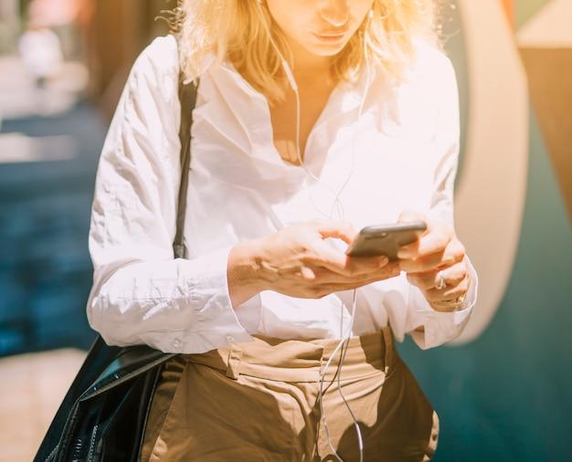 屋外で携帯電話を使用して金髪の若い女性の半ばセクション 無料写真