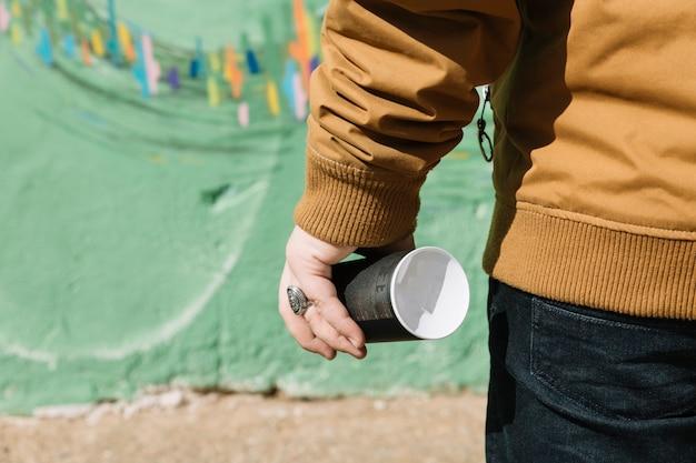 Средняя часть человека, держащего аэрозоль, может стоять перед стенами граффити Бесплатные Фотографии