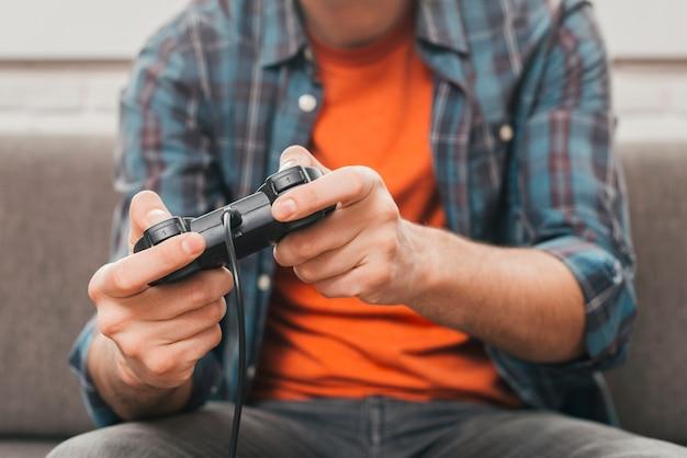 Средняя часть человека, играющего в видеоигру с джойстиком Premium Фотографии