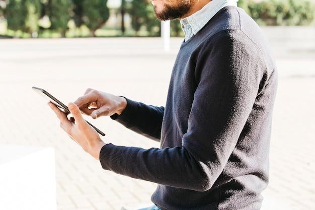 Средняя часть человека, сидящего в парке с помощью мобильного телефона с сенсорным экраном Бесплатные Фотографии