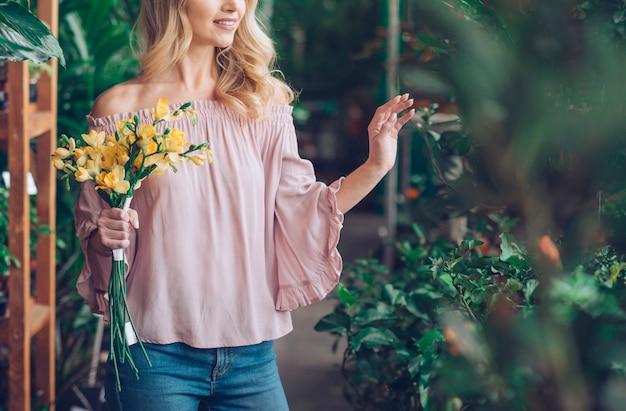 植物保育園で黄色い花の花束を保持している若い女性の半ばセクション 無料写真