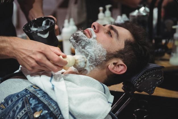 クライアントのあごひげにクリームを塗る床屋の中央部分 無料写真
