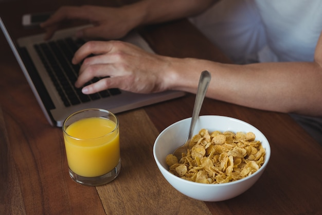 Средняя часть человека, использующего ноутбук во время завтрака в спальне Бесплатные Фотографии