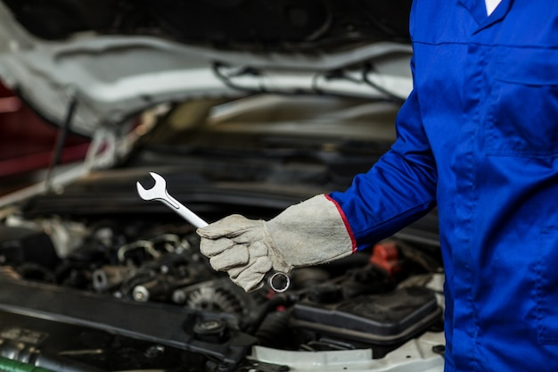 Mid-section of mechanic holding wrench tool Free Photo
