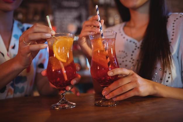 Средняя часть двух молодых женщин, пьющих коктейльные напитки Premium Фотографии