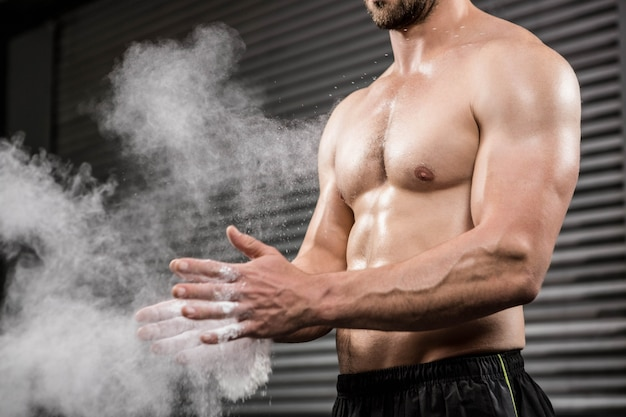 Mid section of shirtless man clapping hands with talc at the crossfit gym Premium Photo