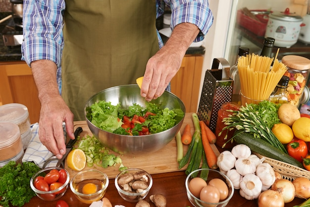 Mid section of unrecognizable man in apron adding lemon juice to the fresh salad Free Photo
