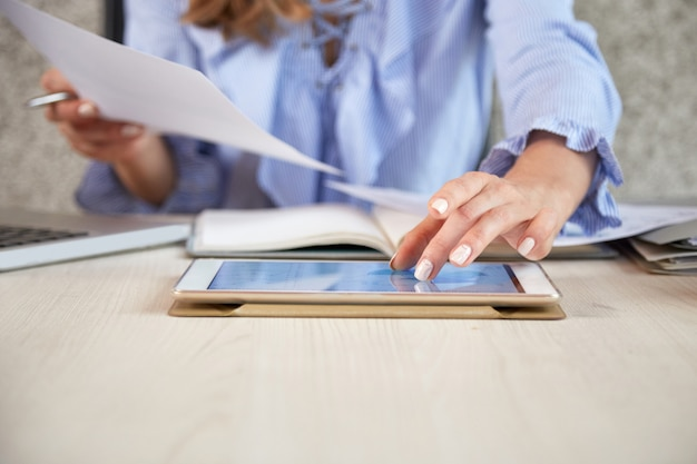 Mid section of unrecognizable woman working with tablet pc at the office desk Free Photo