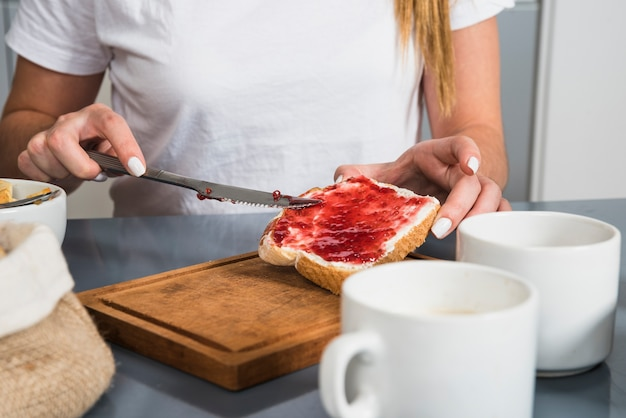 Mid section of a woman applying red jam on bread with butter knife Free Photo